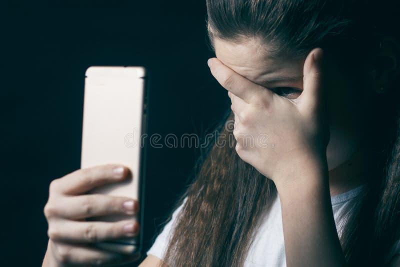 Młoda smutna podatna dziewczyna używa telefon komórkowego i desperackiego cierpienia onlinego nadużycia cyberbullying podkradając obrazy stock