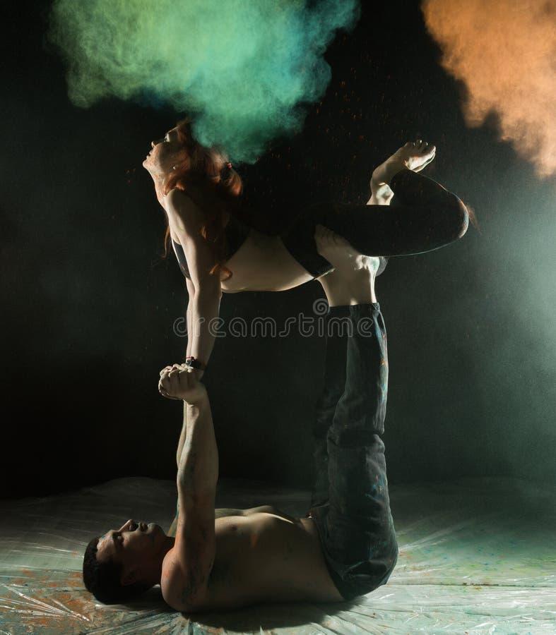 Młoda sport para robi acroyoga ćwiczy w ciemnym pokoju z kolorowym dymem zdjęcie royalty free