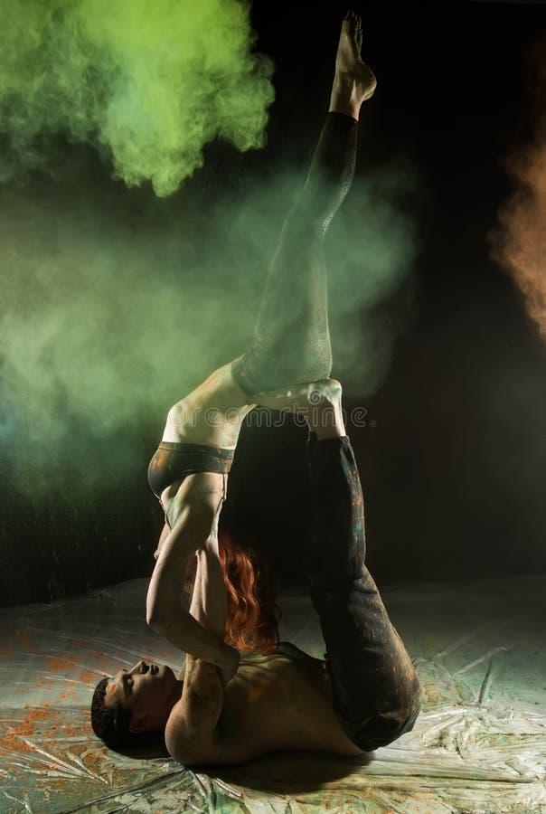 Młoda sport para robi acroyoga ćwiczy w ciemnym pokoju z kolorowym dymem zdjęcia royalty free
