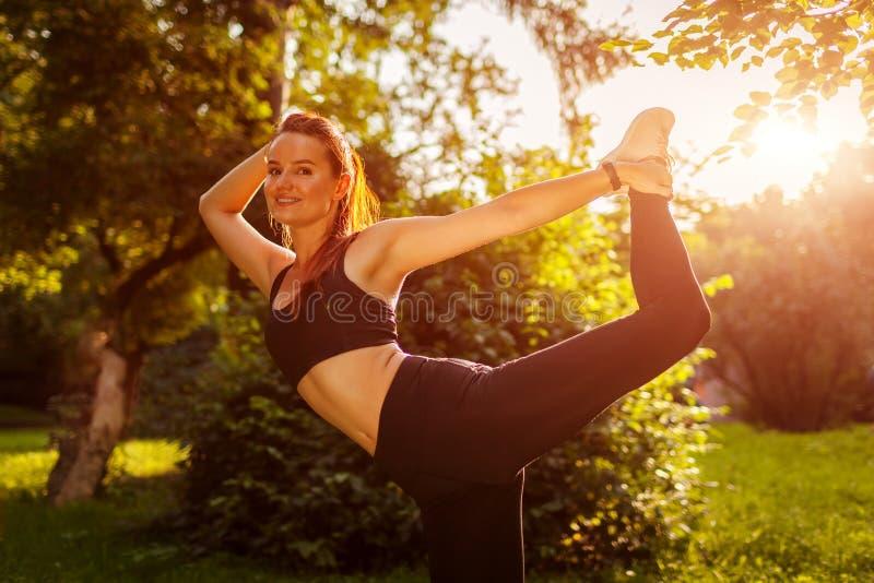 Młoda sportive kobieta robi ćwiczeniom w lato parku Sportsmenka rozciąga jej nogę podnosi mnie behind fotografia royalty free