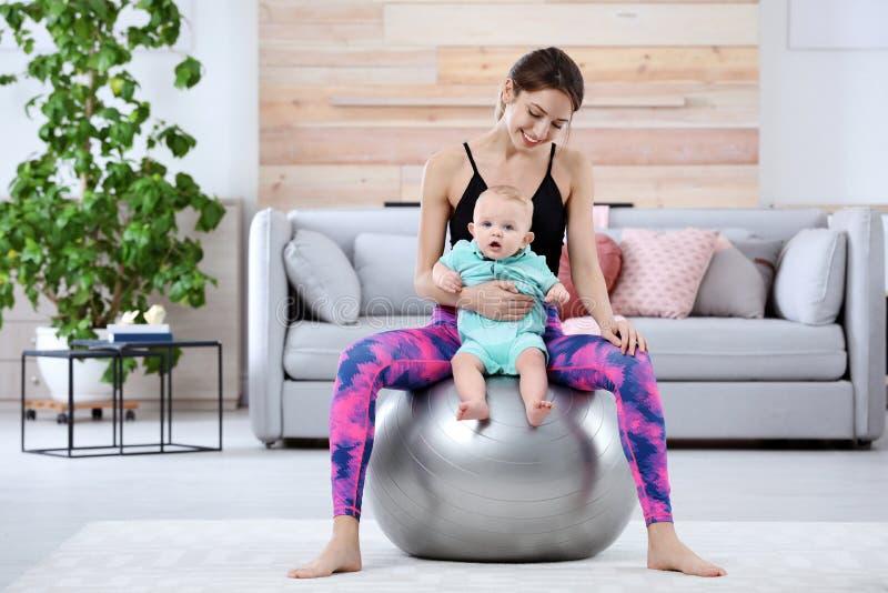 Młoda sportive kobieta robi ćwiczeniu z jej synem w domu zdjęcia royalty free