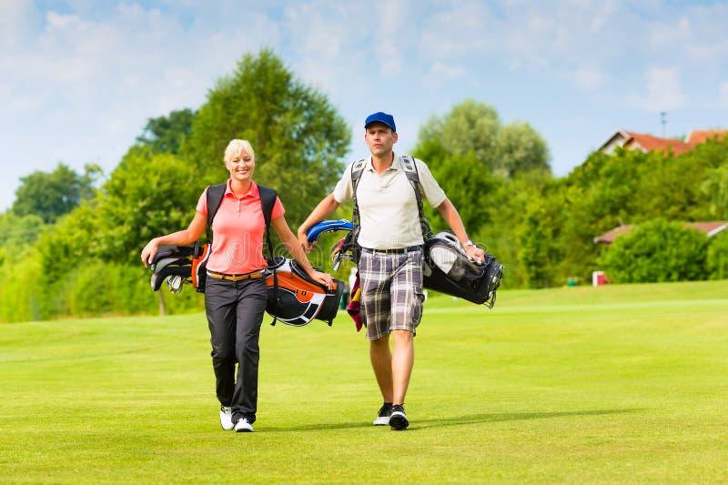 Młoda sportive para bawić się golfa na kursie obraz stock