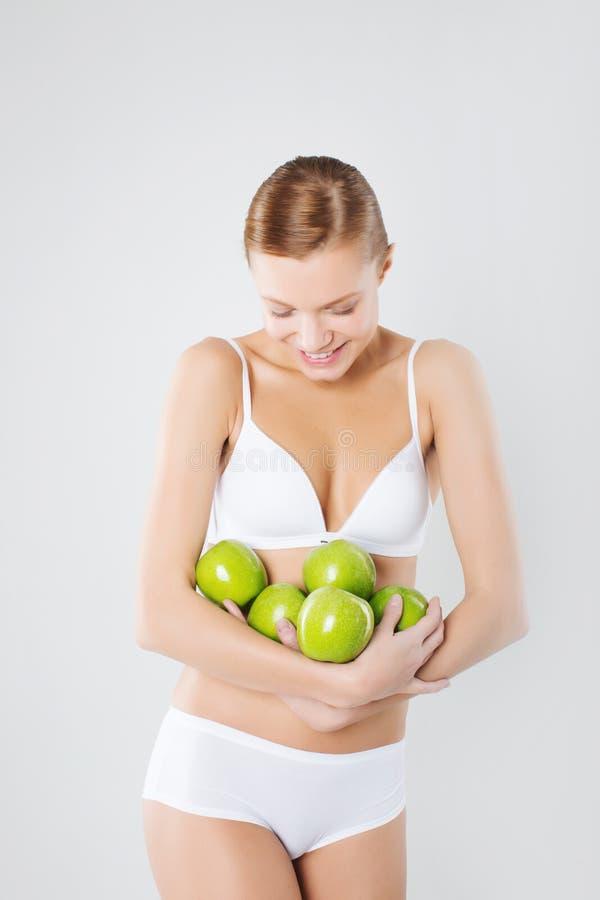 Młoda sportowa dziewczyna trzyma zielonego jabłka diety sprawność fizyczna zdjęcie royalty free