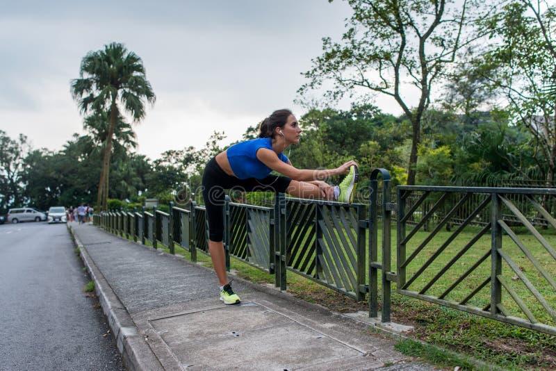 Młoda sportowa kobieta robi nagrzaniu ćwiczy przy drogą przed biegać, rozciąganie ona nogi na ogrodzeniu obraz stock