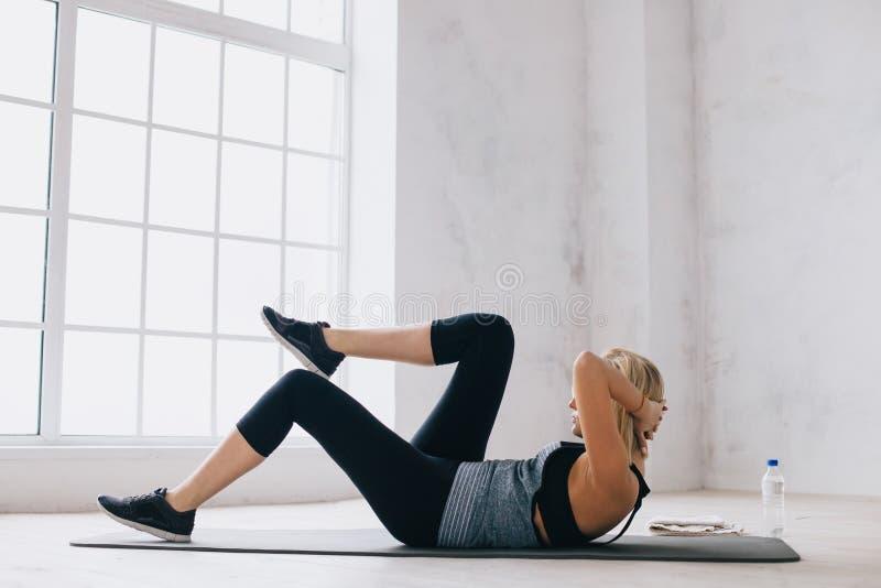 Młoda sportowa kobieta robi prasowemu ćwiczeniu na macie w domu obrazy stock