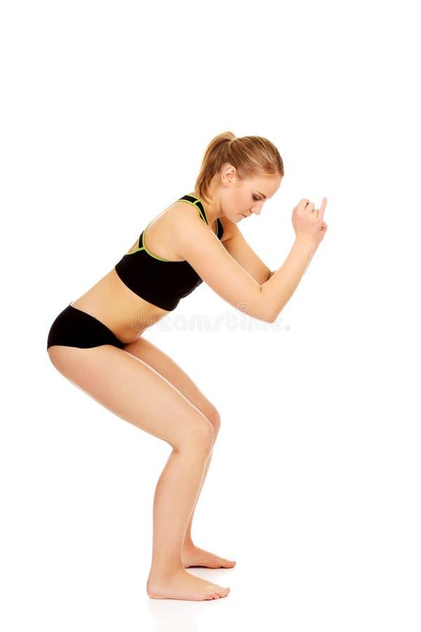 Młoda sportowa kobieta wykonuje kucnięcia zdjęcia stock