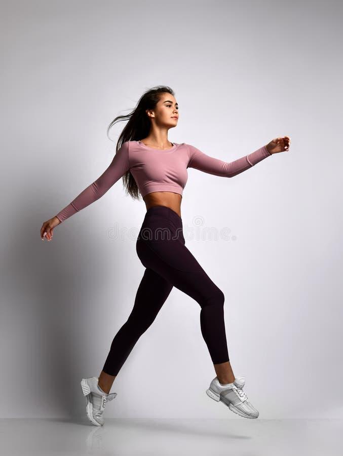Młoda sportowa kobiety brunetki dziewczyna w w dobrym stanie w modnym sportswear odprowadzeniu w gym mundurze robi cardio ćwiczen zdjęcia stock