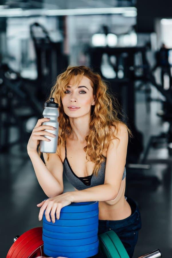 Młoda sportowa kobiety woda pitna w gym zdjęcie royalty free