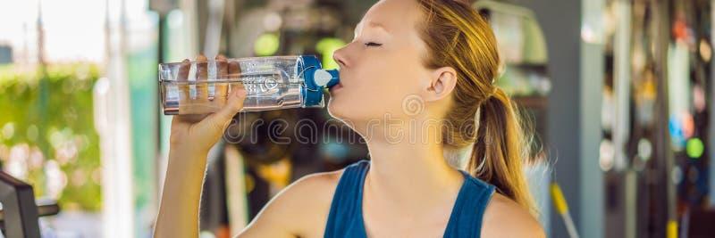 Młoda sportowa kobiety woda pitna w gym sztandarze, DŁUGI format zdjęcie stock