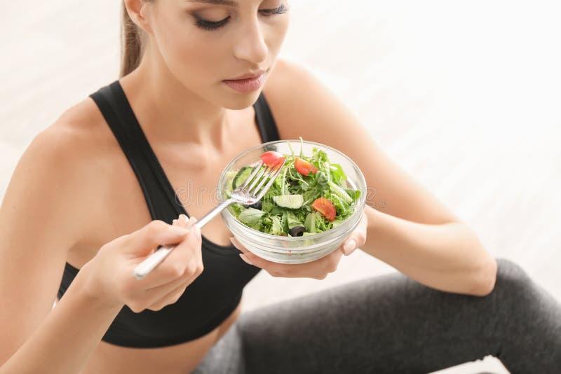 Młoda sporty kobieta je świeżego warzywa sałatki w domu obraz royalty free