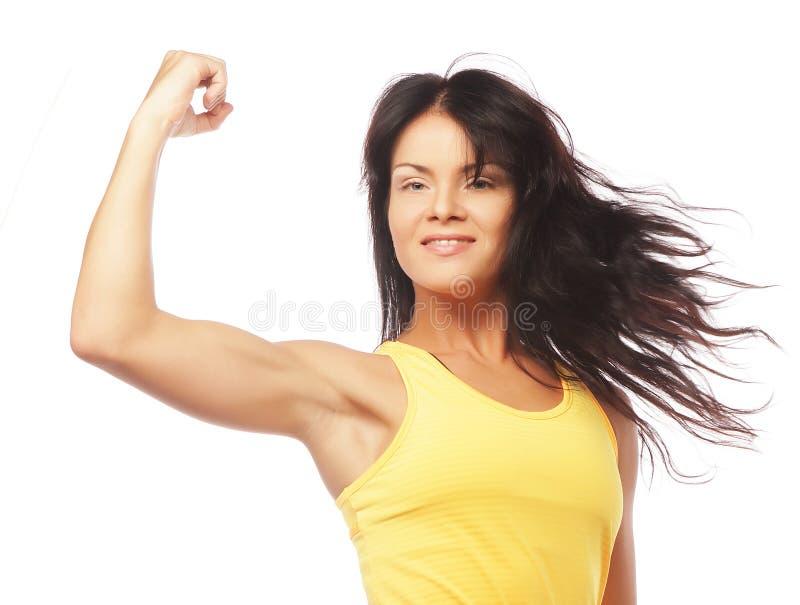 Młoda sporty kobieta napina jej bicepsy zdjęcie stock
