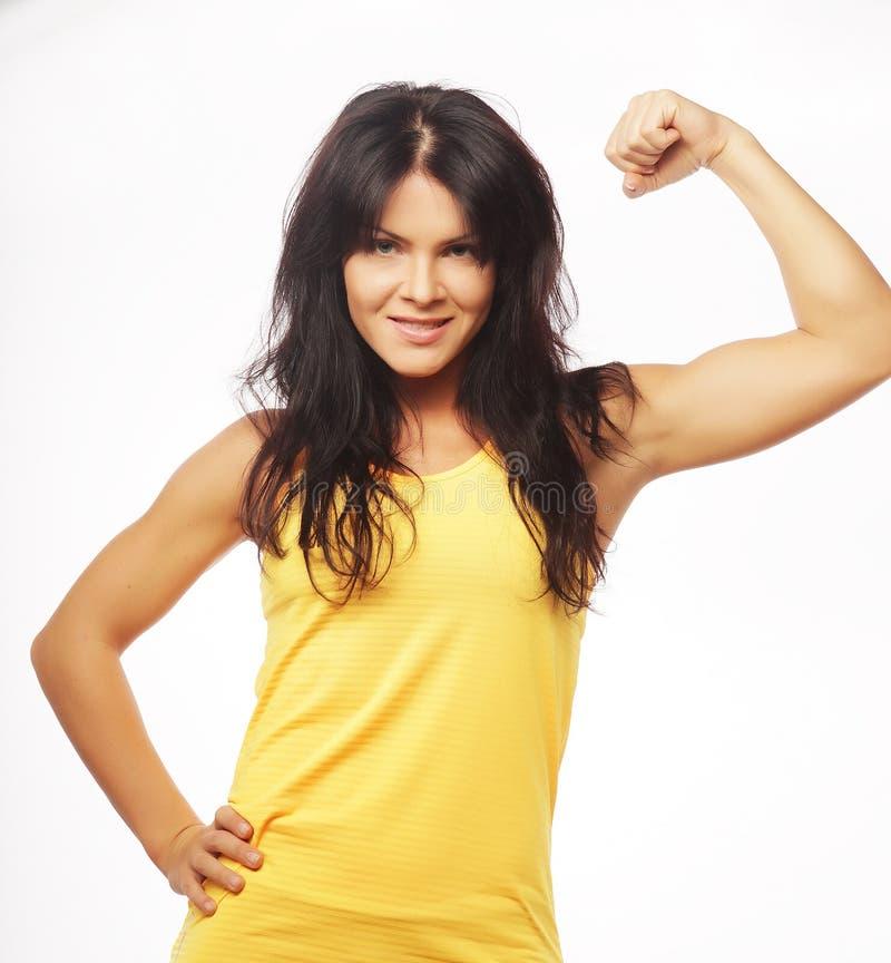 Młoda sporty kobieta napina jej bicepsy fotografia stock