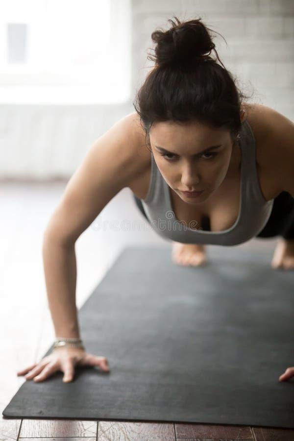Młoda sporty kobieta robi prasy podnosi ćwiczenie, biały loft studio obraz royalty free