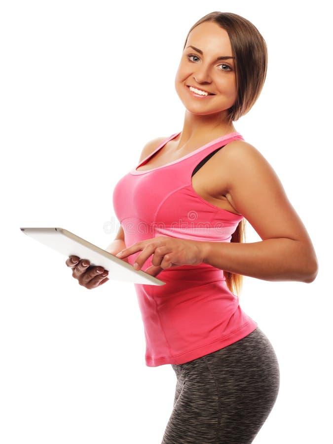 Młoda sporty kobieta używa cyfrową pastylkę fotografia stock