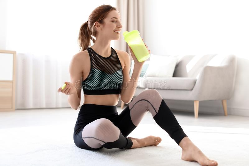Młoda sporty kobieta z butelką proteinowy potrząśnięcia obsiadanie obraz stock