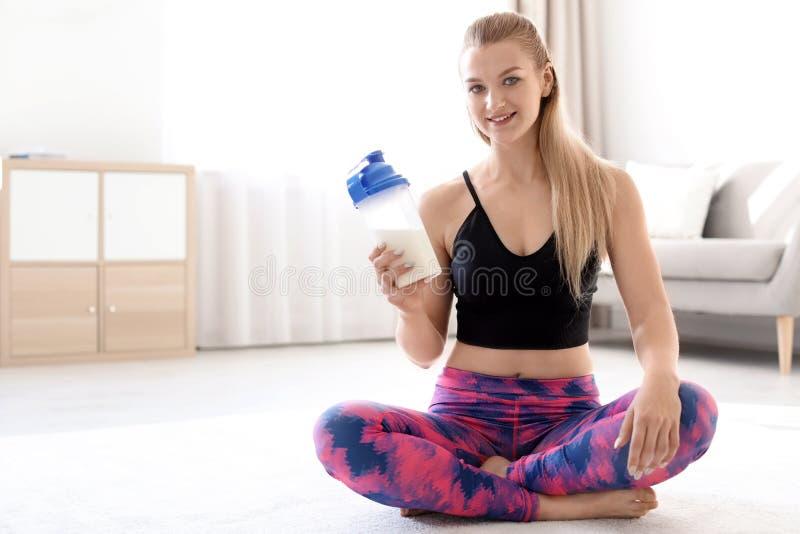 Młoda sporty kobieta z butelką proteinowy potrząśnięcia obsiadanie na podłodze w domu zdjęcie stock