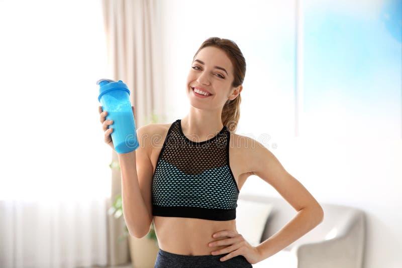 Młoda sporty kobieta z butelką proteinowy potrząśnięcie zdjęcia royalty free