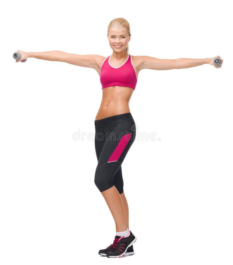 Młoda sporty kobieta z lekkimi dumbbells obraz stock