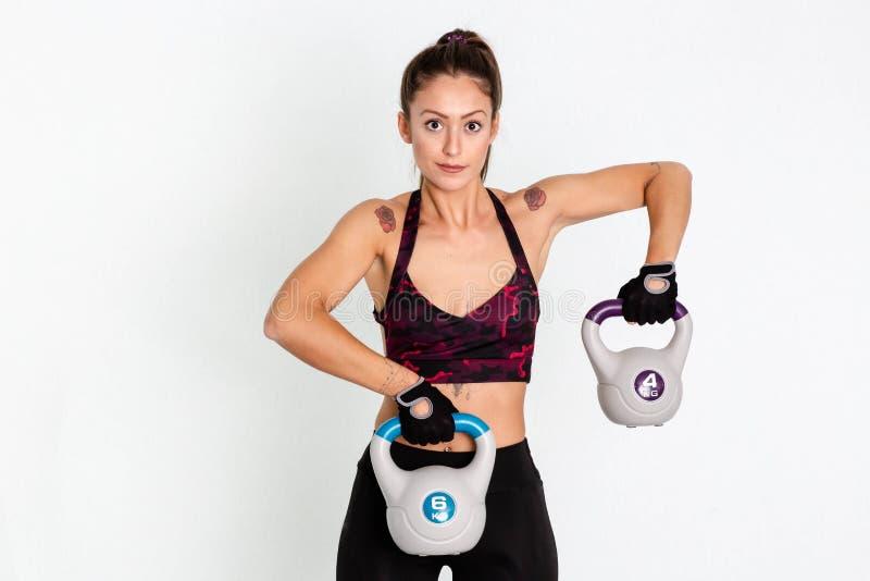 Młoda sprawność fizyczna womnging kettlebells podczas crossfit szkolenia niezrównoważenie obrazy royalty free