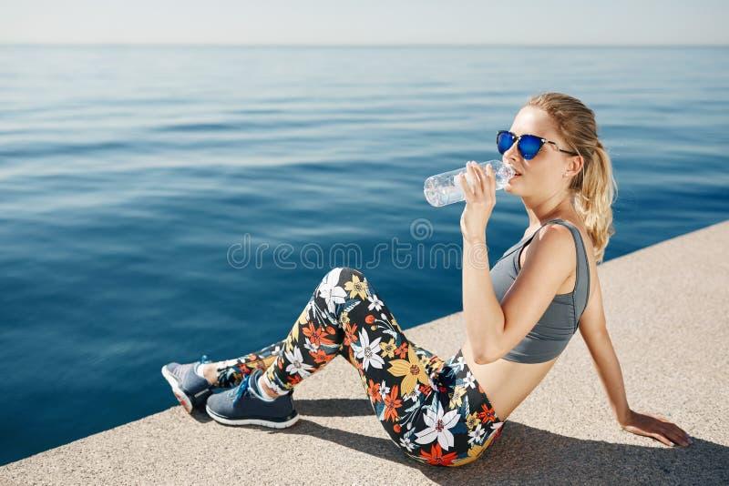 Młoda sprawności fizycznej blondynki kobiety woda pitna po biegać przy plażą zdjęcia royalty free