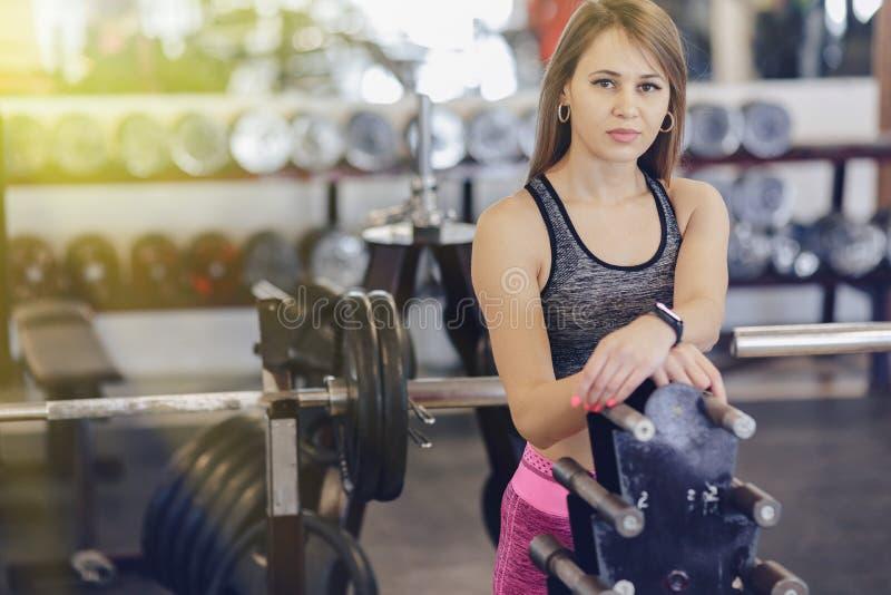 Młoda sprawności fizycznej dziewczyna w gym między symulantami obraz royalty free