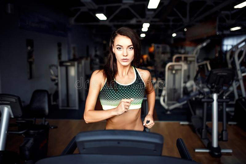 Młoda sprawności fizycznej kobieta robi cardio ćwiczeniom przy gym bieg na karuzeli obrazy stock