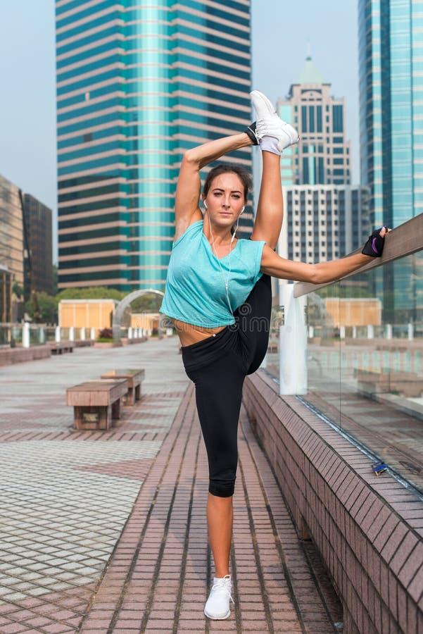 Młoda sprawności fizycznej kobieta robi stojący rozszczepionego ćwiczenie na miasto ulicie Sporty dysponowanej dziewczyny pracują fotografia stock