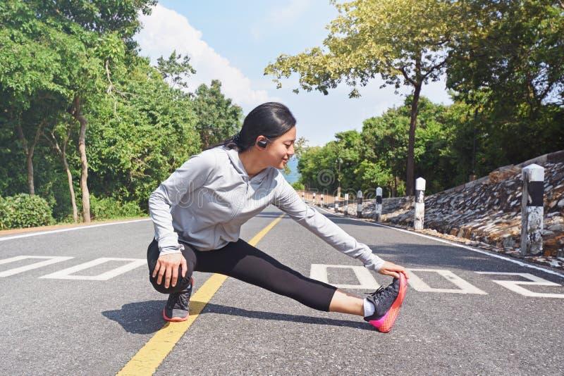 Młoda sprawności fizycznej kobieta rozciąga jej nogę na drodze w ranku zdjęcie stock