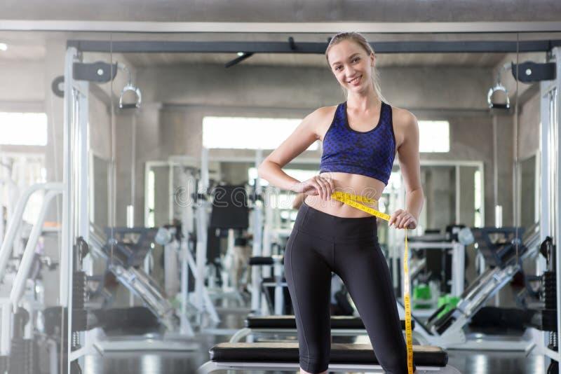 młoda sprawności fizycznej kobieta w sportswear pomiarowej talii z taśmą w sporta gym fotografia royalty free