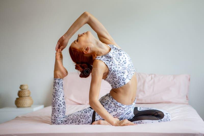 Młoda sprawności fizycznej kobieta w sportwear ćwiczy joga na łóżku w sypialni w ranku w domu sport dziewczyna robi Jeden Iść na  obrazy royalty free