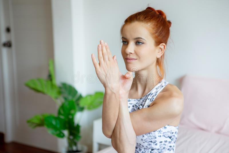 Młoda sprawności fizycznej kobieta w sportwear ćwiczy joga na łóżku w sypialni w ranku w domu sport dziewczyna robi rękom krzyżow zdjęcie stock