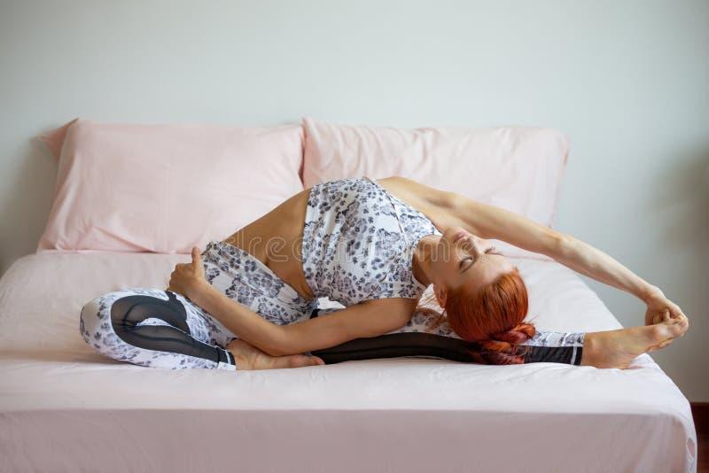 Młoda sprawności fizycznej kobieta w sportwear ćwiczy joga na łóżku w sypialni w ranku w domu sport dziewczyny rozciągania nogi i obrazy royalty free