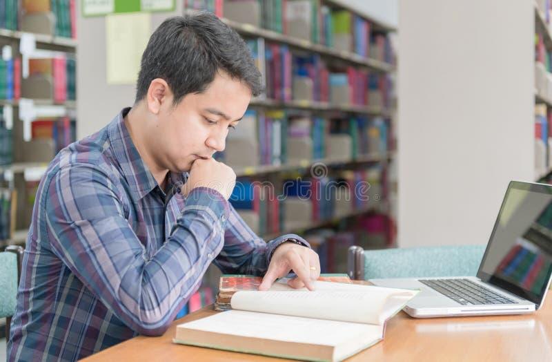 Młoda studencka czytelnicza książka przy biblioteką fotografia stock