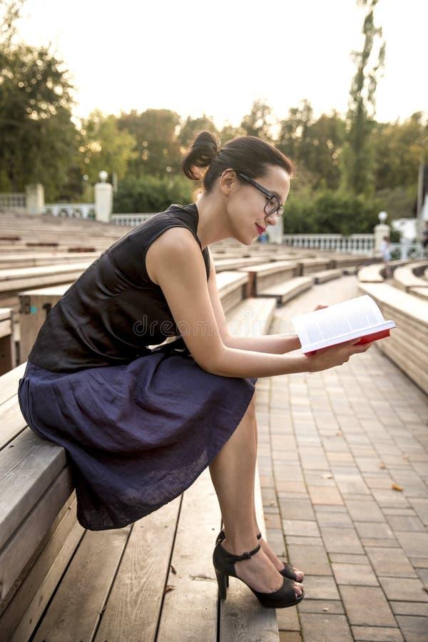 Młoda studencka dziewczyna czyta książkę w parku obraz stock