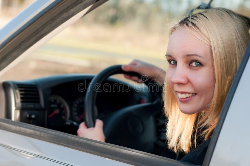 Młoda studencka dziewczyna jedzie samochód obrazy stock