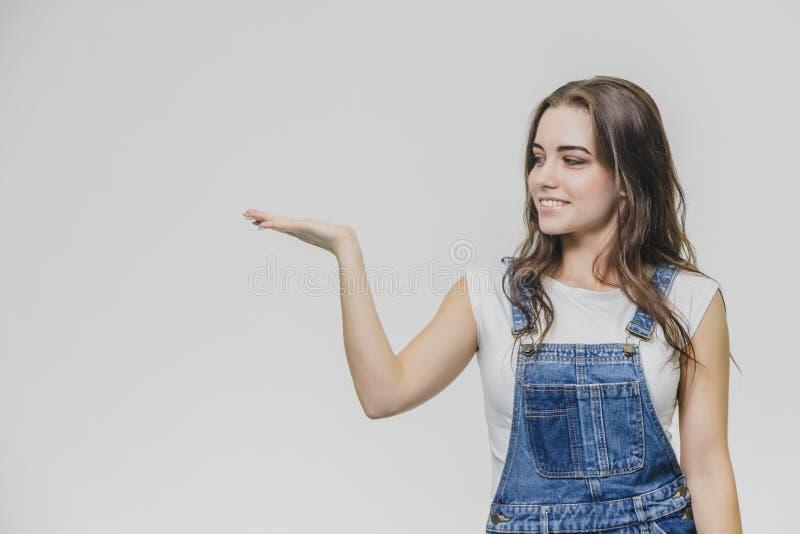 Młoda studencka dziewczyny pozycja na białym tle Ubierający w białych koszulki i drelichu kombinezonach Podczas to, stawiający je zdjęcia stock