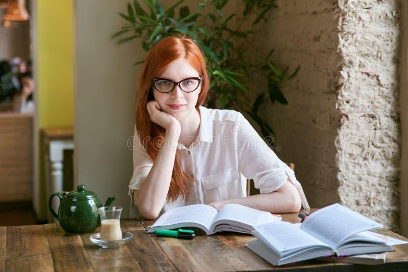 Młoda studencka dziewczyny uczennica robi pracie domowej pisze dyplomu a zdjęcie stock