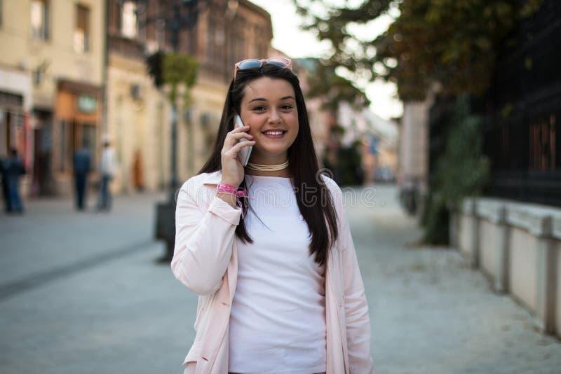 Młoda stylowa kobieta rozmawiająca na smartfonie na zewnątrz fotografia stock