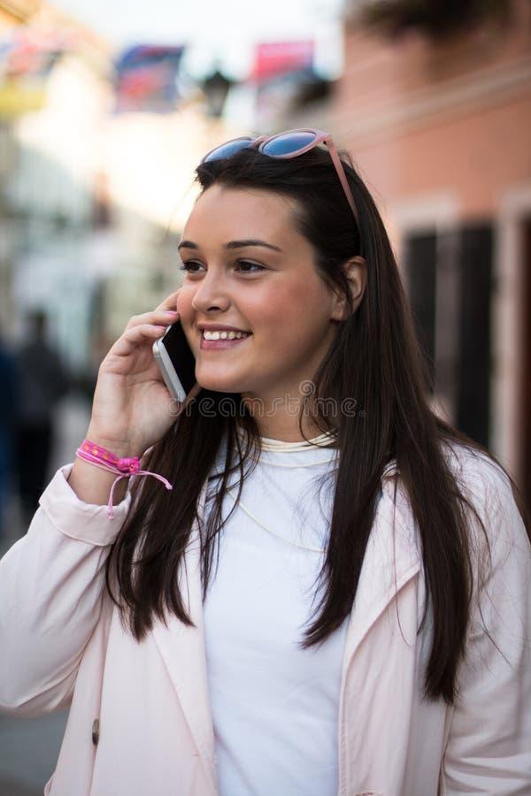 Młoda stylowa kobieta rozmawiająca na smartfonie na zewnątrz obraz royalty free