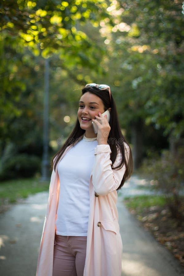 Młoda stylowa kobieta rozmawiająca na smartfonie na zewnątrz obrazy stock