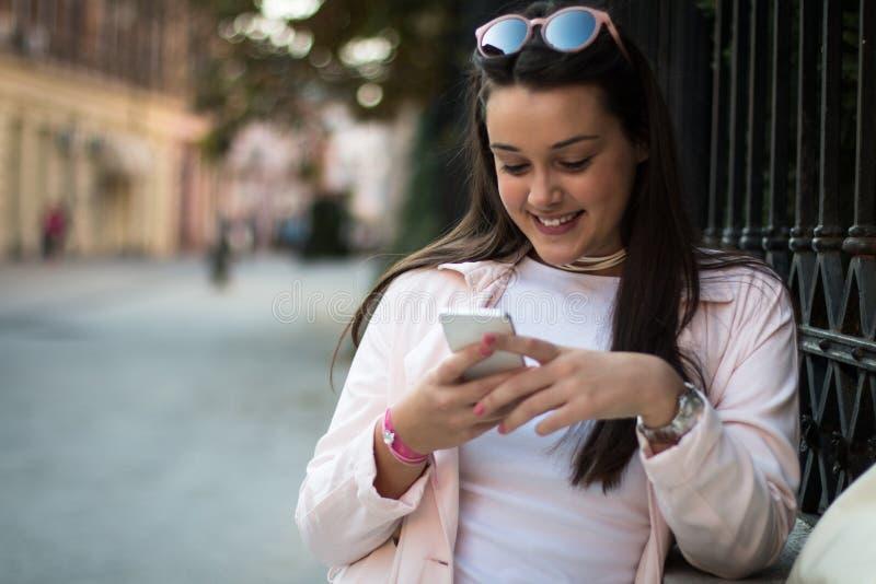 Młoda stylowa kobieta używająca smartfona na zewnątrz na ulicy obraz royalty free