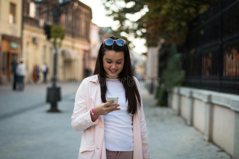 Młoda stylowa kobieta używająca smartfona na zewnątrz na ulicy zdjęcie royalty free