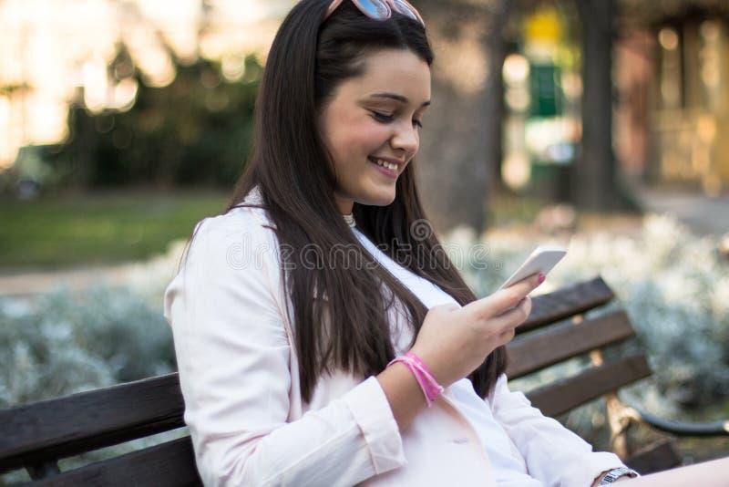 Młoda stylowa kobieta używająca smartfona na zewnątrz w parku fotografia stock