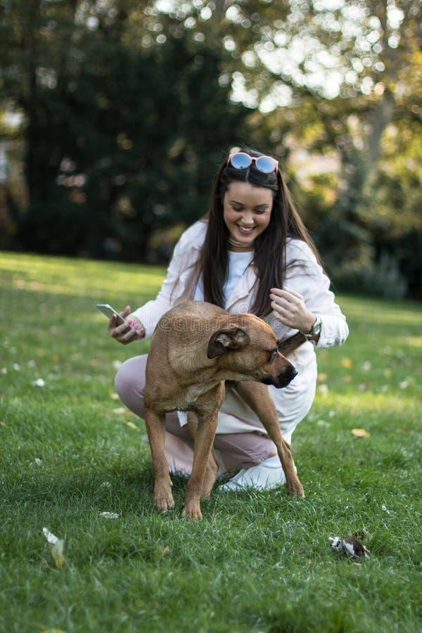 Młoda stylowa kobieta z psem w parku obraz royalty free