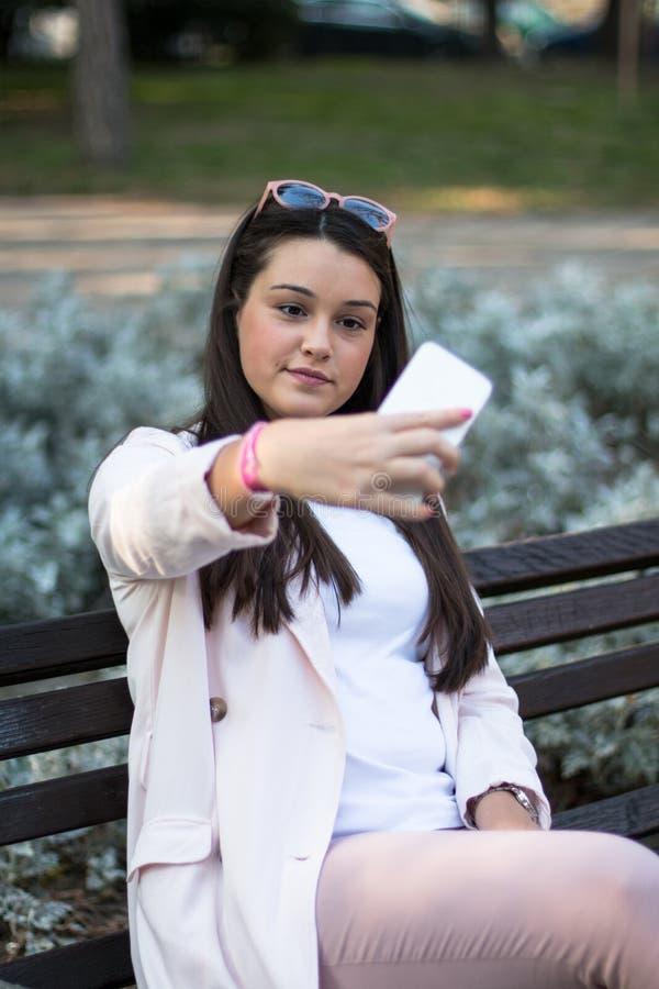Młoda stylowa kobieta zabiera selfie z telefonem w parku zdjęcia stock