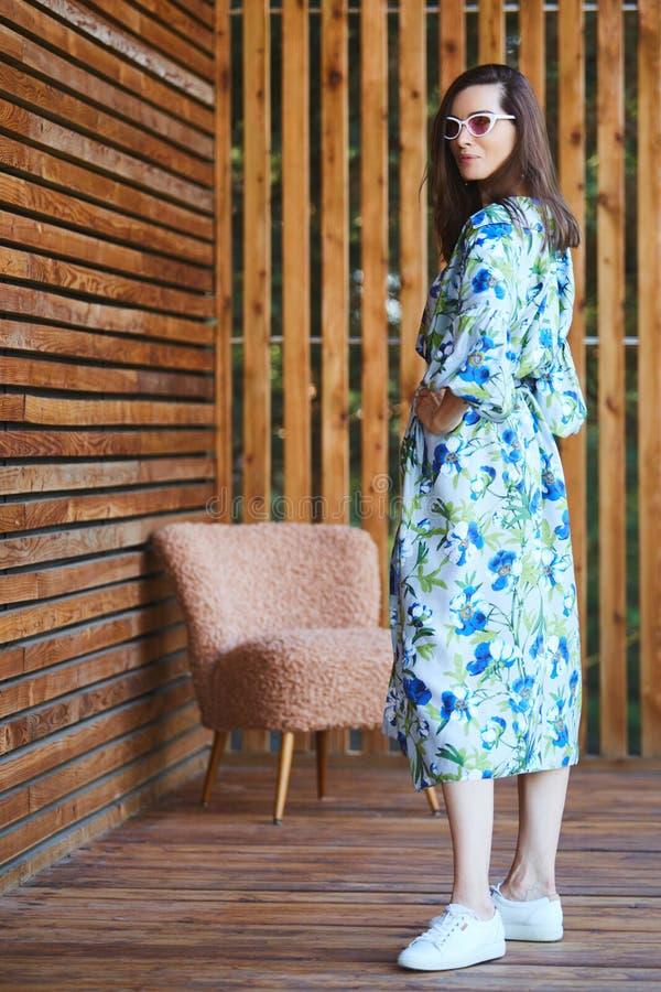 Młoda, stylowa, seksowna kobieta w letniej sukience stojąca na drewnianym tarasie w tropikalnym hotelu, tło palm, długa czarna zdjęcia royalty free