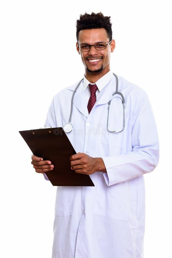 Młoda szczęśliwa Afrykańska mężczyzna lekarka ono uśmiecha się podczas gdy trzymający schowek zdjęcia stock