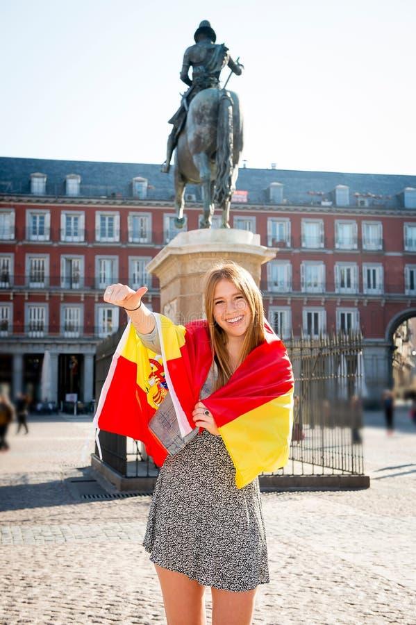 Młoda szczęśliwa atrakcyjna wekslowego ucznia dziewczyna ma zabawę w grodzkim odwiedza Madryt mieście pokazuje Hiszpania flaga obrazy royalty free
