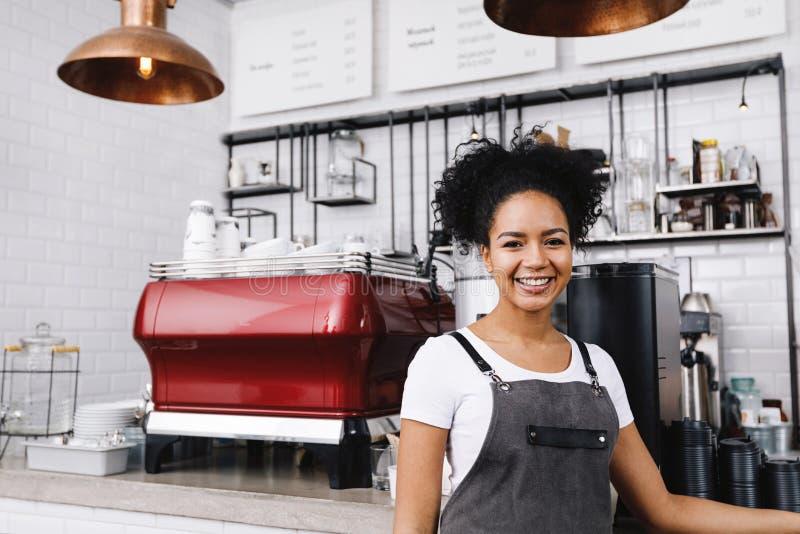 Młoda szczęśliwa barista pozycja w kawiarni obrazy royalty free