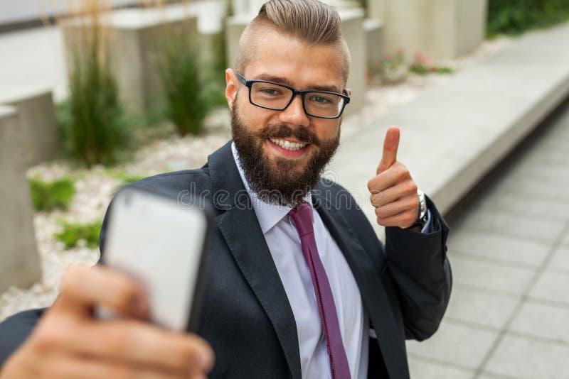 Młoda szczęśliwa brodata biznesmen pozycja na zewnątrz budynku biurowego fotografia stock